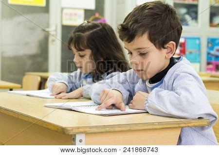 Two Cute Little Preschool Kids In A Classroom