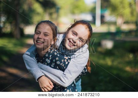Two girls sisters or girlfriends having fun outdoors. Portraits.