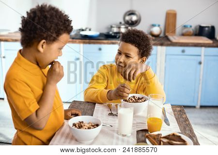 Pleasant Conversation. Upbeat Pre-teen Boys Sitting At The Table And Chatting With Each Other While