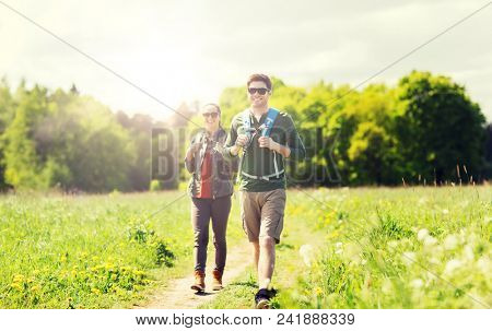 travel, hiking, backpacking, tourism and people concept - happy couple with backpacks and walking along country road outdoors