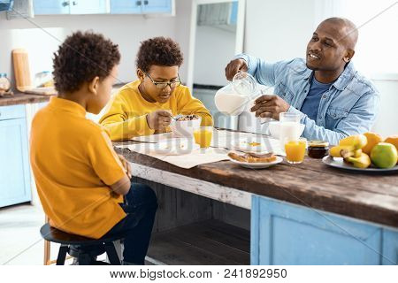 Discussing Plans. Upbeat Young Man Pouring A Glass Of Milk And Chatting With His Sons While They All