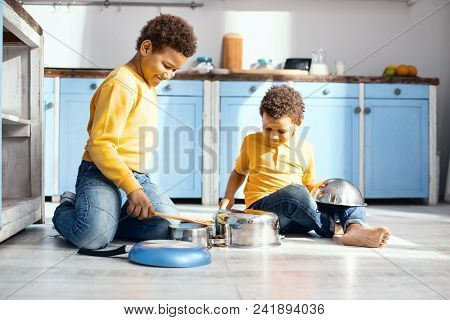 Funny Cacophony. Upbeat Little Kids Sitting On The Kitchen Floor And Drumming On Saucepans, Pretendi