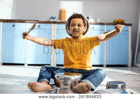 Little Drummer. Upbeat Little Drummer Sitting On The Kitchen Floor And Pretending To Be A Drummer Wh