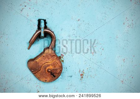 Old Rusty Lock Without A Key On A Blue Background.