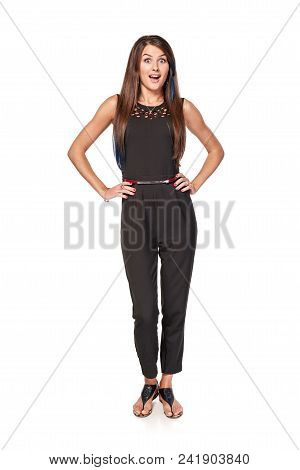 Surprised Woman In Black Jumpsuit Standing In Full Length With Hands On Hips Looking With With Wide-