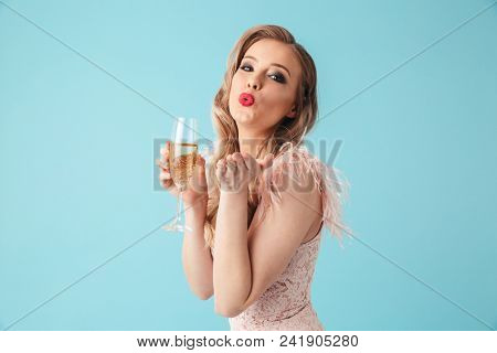 Happy sensual blonde woman in dress posing with glass of champagne while sends air kiss at the camera over pink background