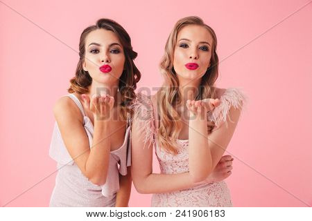Two women in dresses posing together while sends air kisses and looking at the camera over pink background