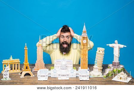 Concept Of Travel - Excited Bearded Man Holds Hands On Head Near Table With Famous Monuments Of Worl