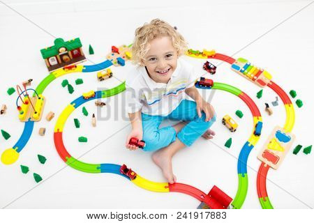 Kids Play With Toy Train Railway. Child Playing With Colorful Rainbow Wooden Trains. Toys For Little