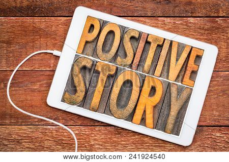 positive story - word abstract in vintage letterpress wood type on a digital tablet against rustic wood