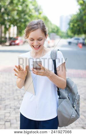 Happy Female Student Walking And Enjoying Mobile Message. Portrait Of Young Caucasian Girl Wearing W