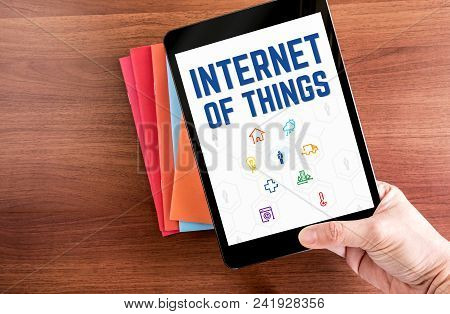 Top View Of Hand Holding Tablet With Internet Of Things (iot) Word With Feature Icon Over Color Note