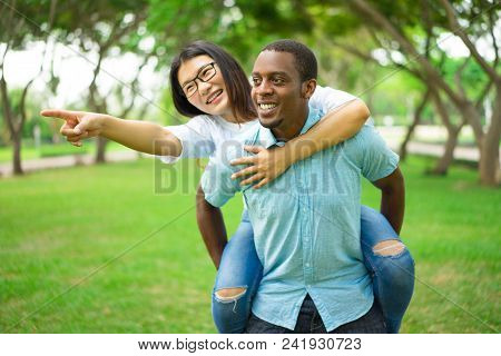 Happy Young Man Giving Piggyback Ride To Girlfriend Or Friend. Asian Woman Wearing Glasses Giving Di
