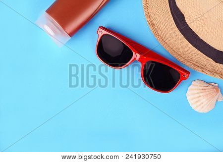 Top View Of Sunglasses, Shells, Starfish, Sunblock And Hat