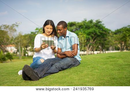 Portrait Of Smiling Students Or Friends Using Touchpad Outdoors. Young Asian Woman And African Ameri