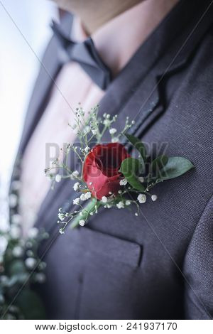 Corsage boutonniere brooch on a man groom suit on wedding day. poster