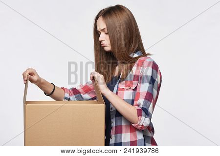 Side View A Discontent Disappointed Girl Opening A Box Looking At Camera