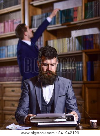 Writing And Literature Concept. Man With Beard And Busy Face Sit In Library And Work With Typewriter