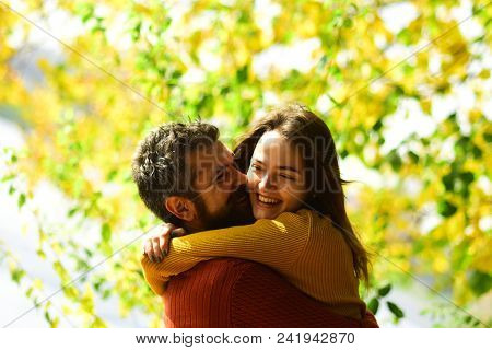 Man and woman with happy faces on autumn trees background. Couple in love cuddles and play in park. Girl and bearded guy or happy lovers on a date kiss and hug. Romance and sunny fall mood concept poster