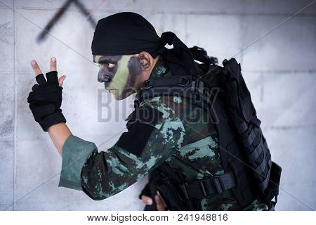 Asian Army Soldier Sending Special Signal To Partner With Weapon In Hand.
