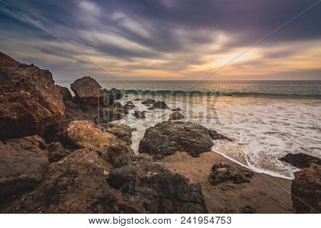 Dramatic Sky At Sunset Along Point Dume State Beach With Waves Crashing Into Rock Formations Along T