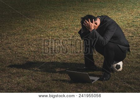 Stressed Businessman With Head In Hands At Soccer Field, Stressed Young Businessman Sitting Outside