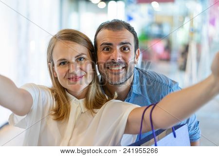 Smiling Middle-aged Couple Taking Selfie Photo In Mall And Looking At Camera With Blurred View In Ba