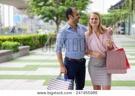 Cheerful Couple Happy About Their Shopping Trip. Stylish Handsome Man With Stubble Carrying Shopping