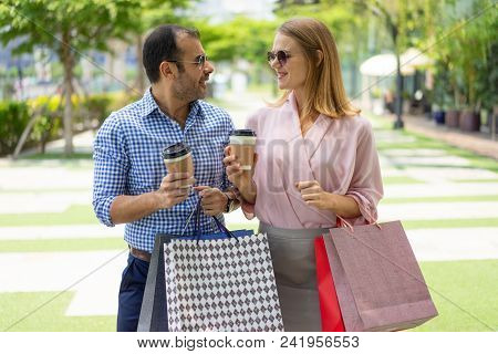 Content Family Couple Walking Outdoors After Shopping. Handsome Man And Beautiful Woman With Paper B