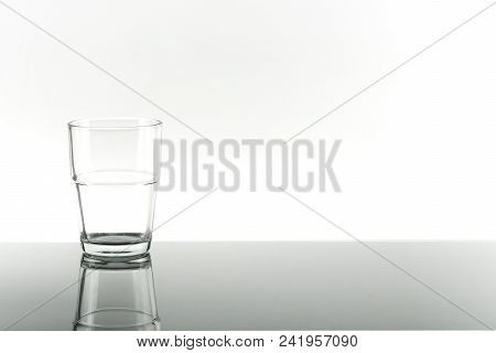 Empty Glass With Reflection Of Crystal Glass From The Table On White Background. Concept Of Nature,