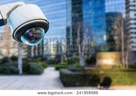 Focus On Security Cctv Camera Or Surveillance System With Buildings On Blurry Background