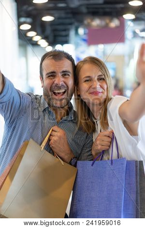 Selfie Portrait Of Joyful Man And Woman Holding Paper Bags In Shop Interior. Cheerful Couple Of Cons