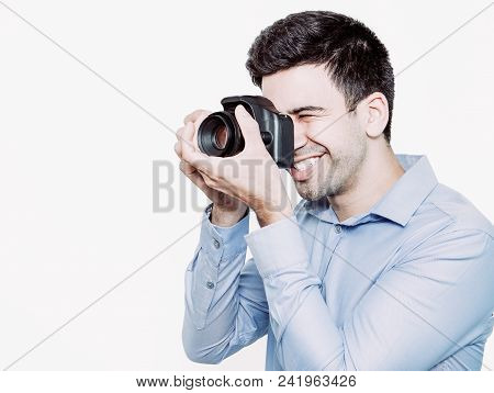 Cheerful Photographer Using Camera To Make Shoot. Positive Young Man Using Manual Focus. He Holding