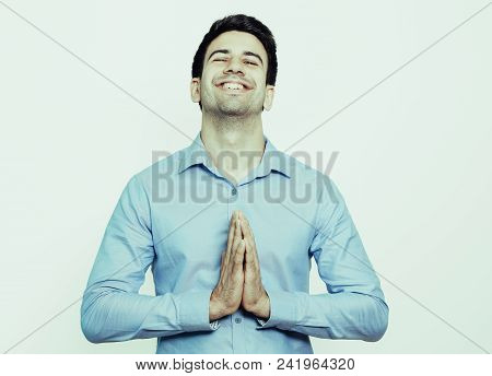 Pleased Young Businessman Meditating And Touching Palms Together. Happy Man With Closed Eyes Thankin