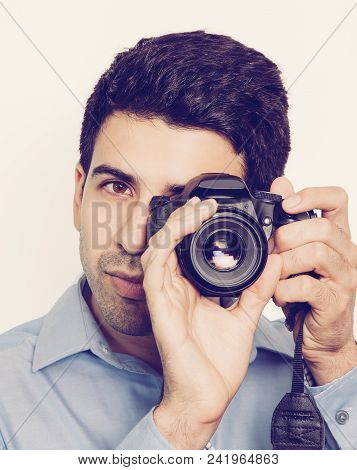 Concentrated Professional Photographer Making Shoot. Young Man Holding Camera And Focusing In Frame.
