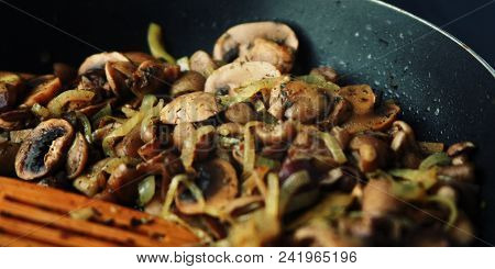 A Skillet With A Fried Mushrooms. Vegan Dish. Fried Mushrooms And Onion In The Frying Pan. European