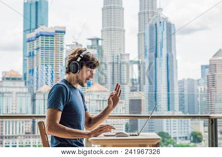 Young Man Teaches A Foreign Language Or Learns A Foreign Language On The Internet On Her Balcony Aga