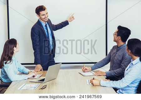 Young Caucasian Business Coach Or Leader Consulting Business Team At Seminar. Businessman Standing A