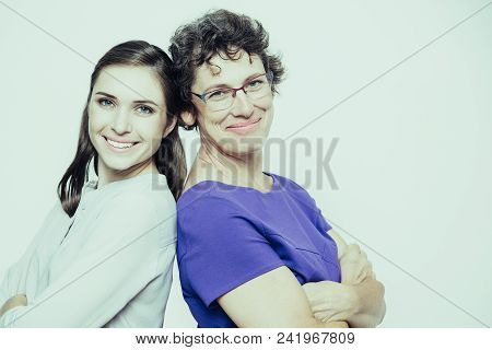 Portrait Of Successful Senior Mother Wearing Glasses And Blue Dress And Her Young Woman Wearing Whit