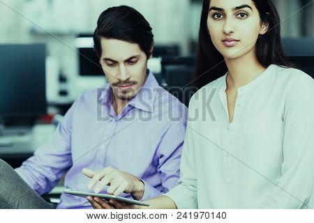 Serious Young Businesspeople, Latin-american Woman And Caucasian Man Working Together. Woman Holding