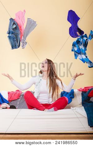 Happy Woman Sitting On Sofa Couch In Messy Living Room Throwing Clothes. Young Girl Surrounded By Ma