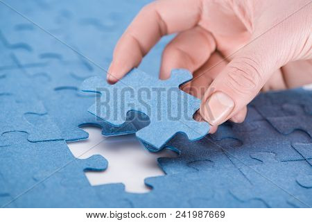 cropped image of businesswoman inserting last missing puzzle, business concept poster