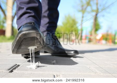 Man Stepping In Chewing Gum On Sidewalk. Concept Of Stickiness
