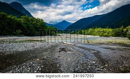Water Flowing Into River Curved Between Mountains. Kamikochi, Japan