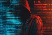 Stereotypical image of computer hacker with hoodie and computer code. Faceless hooded male person lit with red and blue light, conceptual low key image. poster