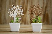 Laser cut wooden tree embellishments in white porcelain flower pots on wooden background poster