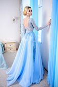 Full length portrait of a magnificent young woman in elegant long blue dress. Luxurious apartments.  Wedding fashion. poster