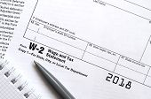 The pen and notebook on the tax form W-2 Wage and Tax Statement. The time to pay taxes poster