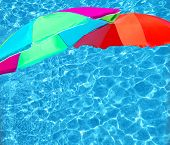 Summer theme concept - bright parasols over turquoise blue pool water surface background. poster