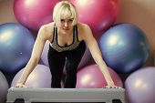 Woman athlete keep arms straight on stepper in gym with colorful fit balls. Endurance, strength and fitness concept. Sport, health, activity poster